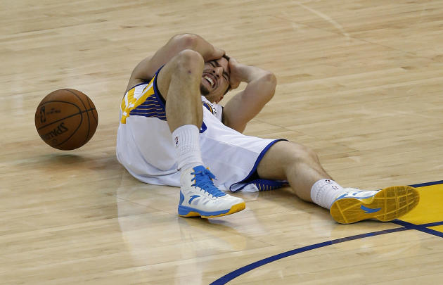 Golden State Warriors guard Klay Thompson lies on the court after being injured during the second half of Game 5 of the NBA basketball Western Conference finals against the Houston Rockets in Oakland,