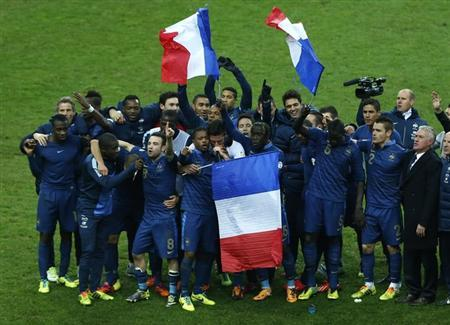 France's soccer team coach Didier Deschamps (R) and team mates celebrate after winning their 2014 World Cup qualifying second leg playoff soccer match against Ukraine at the Stade de France in Saint-Denis near Paris Nove