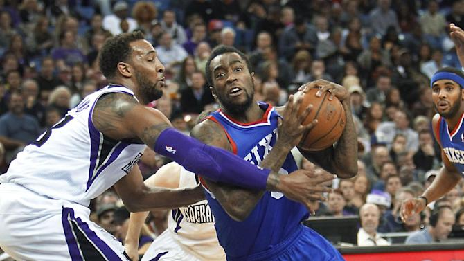 Philadelphia 76ers guard Tony Wroten, right, drives to the basket against Sacramento Kings defender Derrick Williams during the first half of an NBA basketball game in Sacramento, Calif., on Thursday, Jan. 2, 2014
