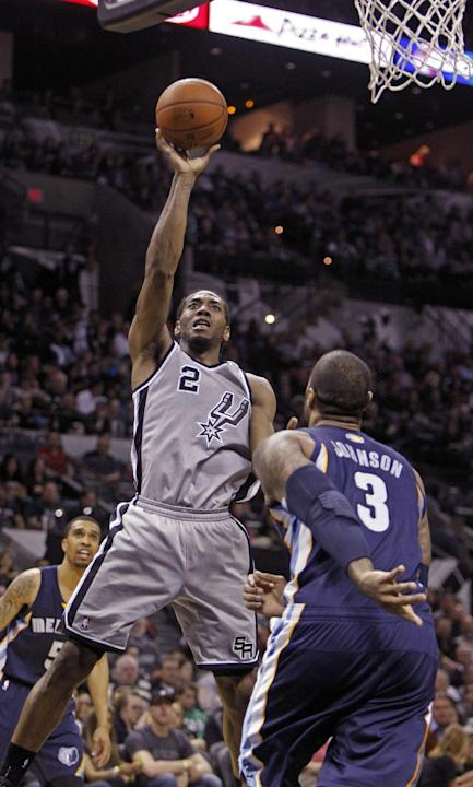 In this April 6, 2014 file photo, San Antonio Spurs' Kawhi Leonard (2) puts up at shot against Memphis Grizzlies'  James Johnson (3) during the second half of an NBA basketball game, in San An