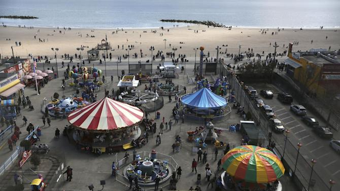 In this Saturday, March 30 2013 photo the beach and visitors to Deno's Famous Wonder Wheel Amusement Park in New York's Coney Island are seen from the park's famous ride.  Despite making the traditional Palm Sunday opening, many of the seasonal businesses at Coney Island are still reeling from the aftermath of Superstorm Sandy. (AP Photo/Mary Altaffer)