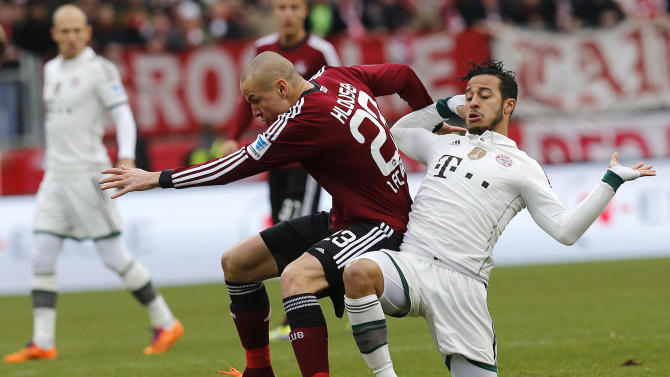 Nuremberg's Adam Hlousek of Czech Republic, left, and Bayern's Thiago Alcantara of Spain challenge for the ball during a German first  division Bundesliga soccer match  between 1.FC Nuremberg and Bayern Munich in Nuremberg, Germany, Saturday, Feb. 8, 2014