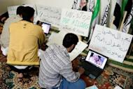 Syrian activists upload pictures and news of unrest to opposition websites as they sit in front of anti-regime posters in the town of Atareb. Twin blasts targeting security buildings killed more than 20 people in the northwest Syrian city of Idlib, a monitoring group said, as the chief UN monitor presses both sides to end more than 13 months of violence