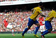 Arsenal's striker Lukas Podolski (L) scores during their English Premier League football match against Southampton at The Emirates Stadium in north London. Arsenal thrashed bottom of the table Southampton 6-1