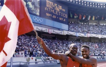 Johnson of Canada celebrates with team mate Williams after winning the men's 100m sprint at the Olympics in Seoul
