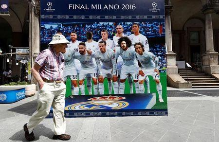 A man walks next to the Real Madrid poster near Duomo square before the UEFA Champions League Final in Milan