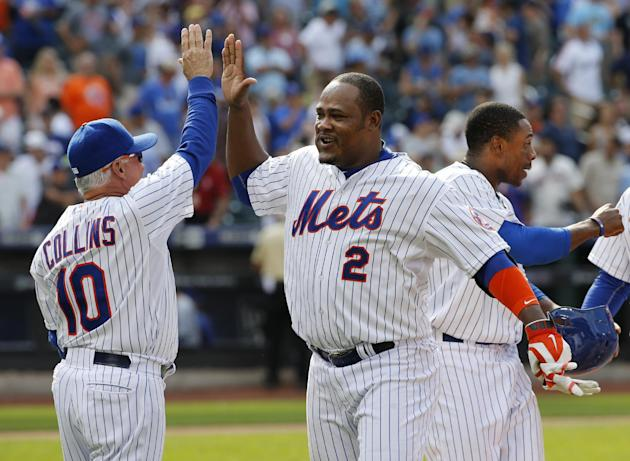 New York Mets manager Terry Collins (10) and the Mets Juan Uribe (2), who joined the team Saturday after a trade, celebrate after Uribe hit a tenth-inning, walk-off single to lift the Mets to a 3-2 vi