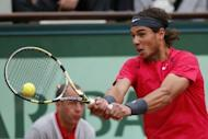 Spain's Rafael Nadal hits a return to Serbia's Novak Djokovic during the French Open men's singles final at Roland Garros in Paris on June 10. Nadal took the first two sets 6-4, 6-3 before Djokovic fought back to win the third 6-2 on a rain-affedted day