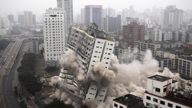 The former Hainan Airlines headquarters topples during a controlled demolition in Haikou