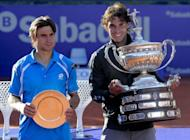 Rafael Nadal (R) celebrates with the trophy after winning the final of the Barcelona Open tennis tournament Conde de Godo against compatriot David Ferrer. Nadal won 7-6, 7-5
