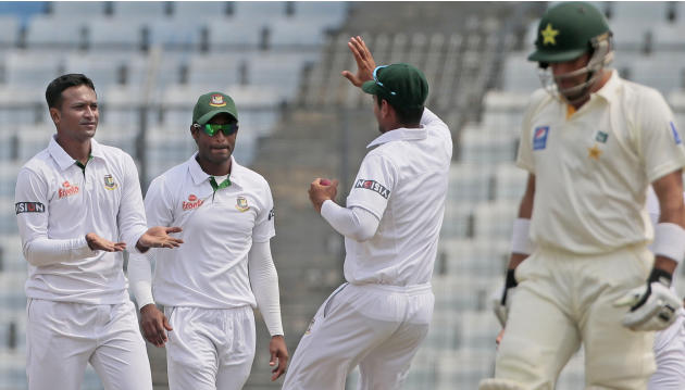 Bangladesh's Shakib Al Hasan, left, celebrates with his teammates the dismissal of Pakistan's captain Misbah-ul-Haq, right, during their second day of the second test cricket match in Dhaka, Banglades