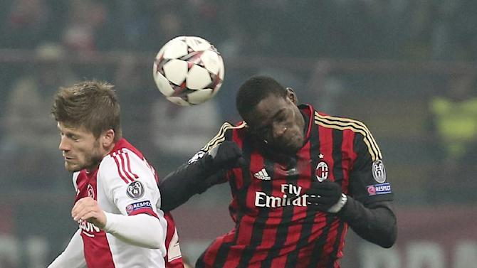 Ajax midfielder Lasse Schone, left, of Denmark, jumps for the ball with AC Milan forward Mario Balotelli during a Champions League, Group H, soccer match between AC Milan and Ajax at the San Siro stadium in Milan, Italy, Wednesday, Dec. 11, 2013
