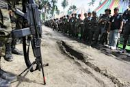 Moro Islamic Liberation Front (MILF) personnel line on a road in Camp Darapanan, Sultan Kudarat in the southern Philippines on July 7, 2012. Philippine Muslim rebel leaders who are negotiating a peace deal with Manila ordered their fighters on Friday not to wear military uniforms or carry guns in public, a spokesman said