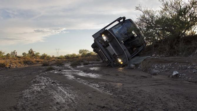 A tour bus lays on its side up against a bank of a wash, Sunday, July 28, 2013, near Dolan Springs, Ariz. The bus, which was carrying 33 passengers and on its way back to Las Vegas from the west rim of the Grand Canyon, was pushed 300 yards down the wash when the driver attempted to drive through flash flood waters flowing across the road. No one on the bus was hurt in the crash which happened as Northern Arizona was hit with a second day of heavy rain. (AP Photo/Julie Jacobson)