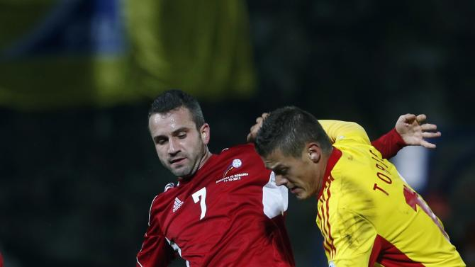 Romania's Torje fights for the ball with Andorra's Pujol during their 2014 World Cup qualifying soccer match at Estadi Comunal in Andorra