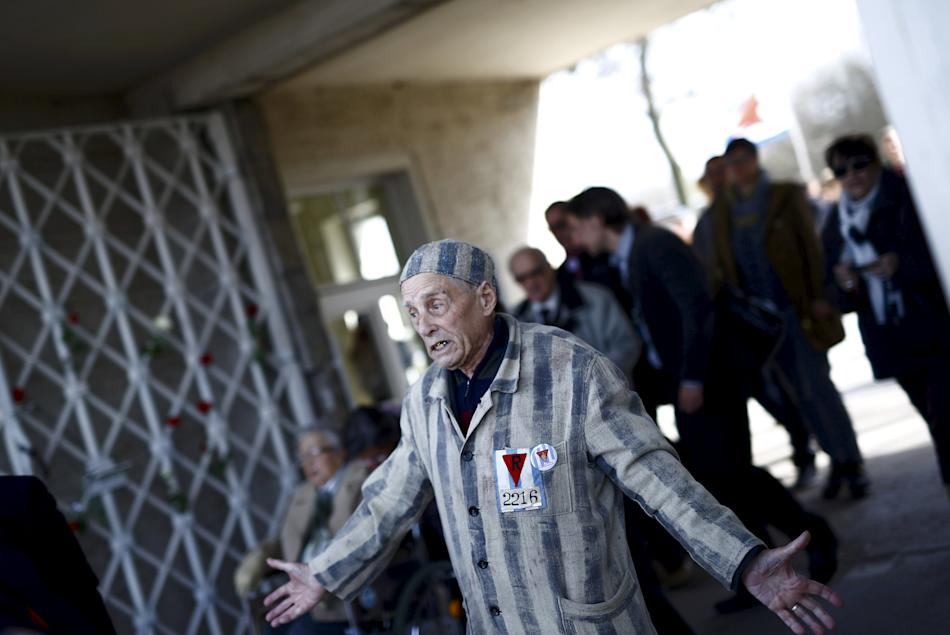 Survivor Alexander Butschuk gestures as he arrives to the former Nazi concentration camp Buchenwald near Weimar