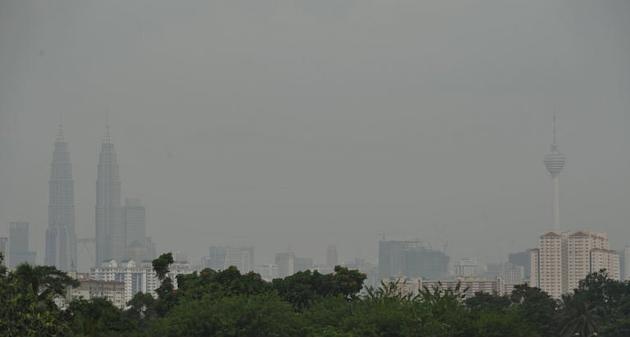 Haze covers Petronas Twin Towers (L) and KL Tower (R) in Kuala Lumpur, on June 16, 2013