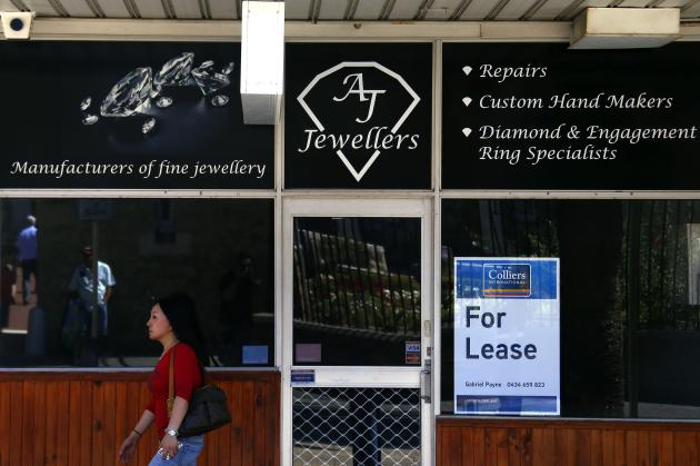 """A woman walks past a former jewellery store displaying a """"For Lease"""" sign in a window in the Western Australian capital city of Perth"""