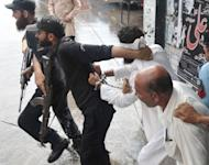 A Pakistani policeman reprimands Islamic cleric Hafiz Mohammed Khalid Chishti after he attempted to shout slogans upon his arrival at a court in Islamabad on September 2. The cleric who accused a young Christian girl of blasphemy in a case that sparked international concern has been remanded in custody on suspicion of evidence-tampering and desecrating the Koran