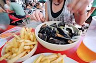 A woman enjoys 'moules-frites' (mussels and French fries) in a restaurant in Lille