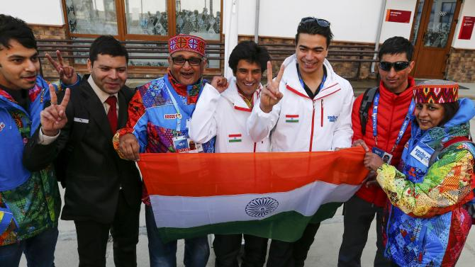 Members of India's national team and volunteers pose with the national flag after the welcoming ceremony for the team in the Olympic athlete's village, which stands on a mountain plateau in Rosa Khutor, during the 2014 Winter Olympic Games