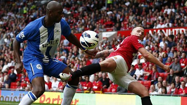 Manchester United's Alexander Buttner (R) challenges Wigan Athletic's Emmerson Boyce during their Premier League match at Old Trafford (Reuters)