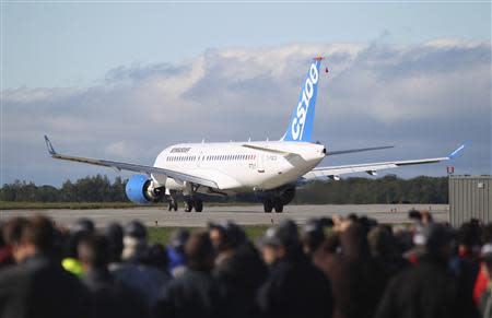 Bombardier employees and guests watch the CSeries aircraft taxi on the runway for its first test flight in Mirabel, Quebec, September 16, 2013. REUTERS/Christinne Muschi