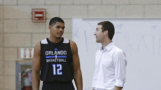Orlando Magic's Tobias Harris (12) talks with Rob Hennigan, the NBA basketball team's general manager, at training camp, Tuesday, Oct. 1, 2013, in Orlando, Fla