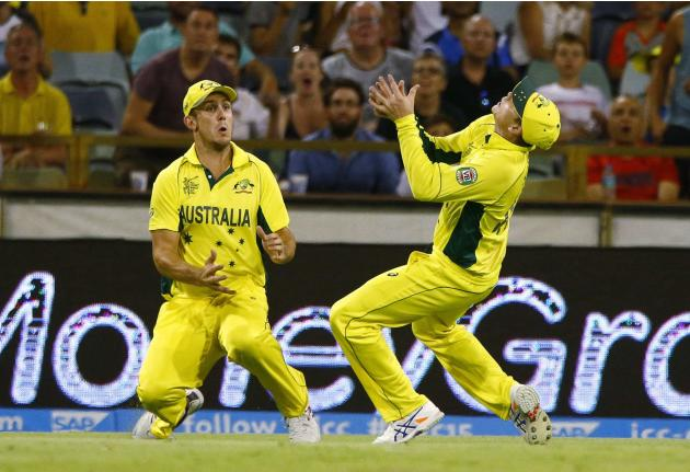 Australia's Steve Smith almost collides into teammate Mitchell Marsh as he catches out Afghanistan's Asghar Stanekzai during their Cricket World Cup match in Perth