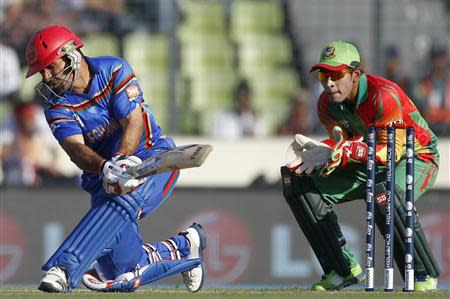Afghanistan's captain Nabi plays a ball as Bangladesh's captain and wicketkeeper Rahim watches during ICC Twenty20 World Cup match in Dhaka