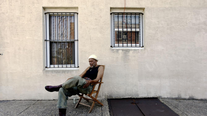 Scoe sits in the shade avoiding the heat of the sun near his home Wednesday, July 17, 2013, in Philadelphia. An excessive heat warning is again in effect for the Philadelphia region with highs expected to head up to the mid-90s. (AP Photo/Matt Rourke)