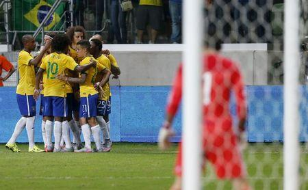 Brazil's players celebrate their second goal against Mexico, scored by Diego Tardelli during a friendly soccer match in Sao Paulo