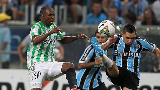 Juan Valencia of Colombia's Atletico Nacional, left, fights for the ball with Para of Brazil's Gremio during a Copa Libertadores soccer game in Porto Alegre, Brazil, Tuesday, Feb.25, 2014