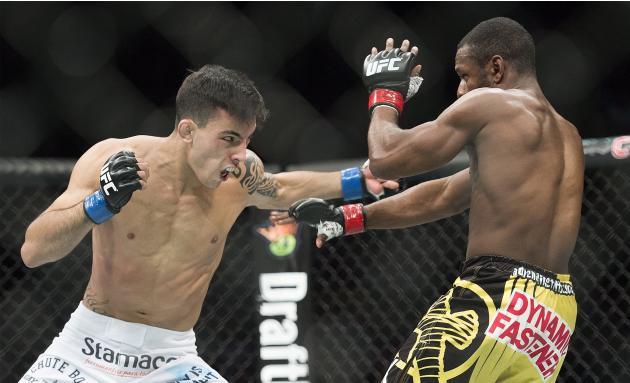 Thomas Almeida, left, from Brazil, lands a blow to the body of Yves Jabouin, from Canada, during their UFC 186 mixed martial arts bantamweight fight in Montreal, Saturday, April 25, 2015. (Graham Hugh