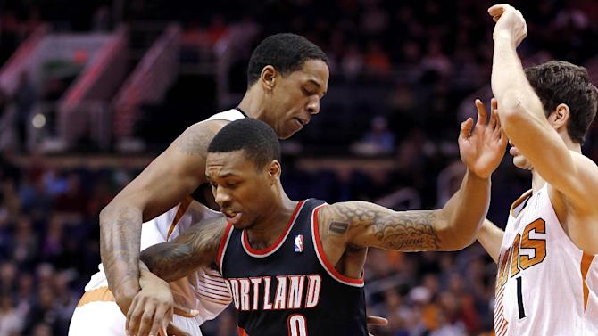 Portland Trail Blazers' Damian Lillard (0) loses the ball as Phoenix Suns' Channing Frye, left, and Goran Dragic, of Slovenia, right, defend during the first half of an NBA basketball game, Wednesday, Nov. 27, 2013, in Phoenix