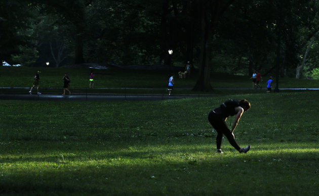 A jogger stretches in a ray of setting sun before starting her run in Central Park, Tuesday, June 16, 2015, in New York. (AP Photo/Julie Jacobson)
