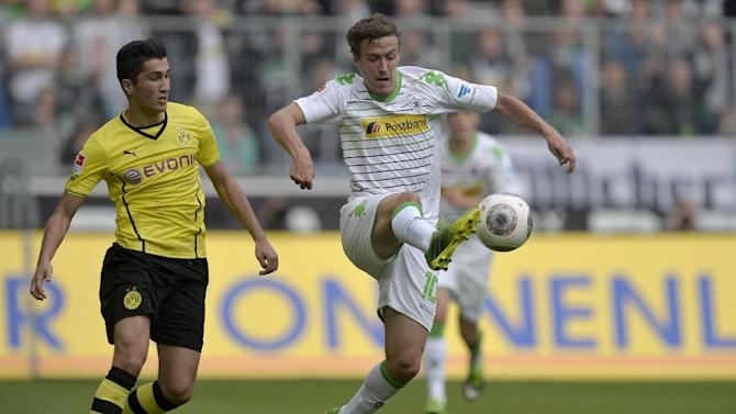 Moenchengladbach's Max Kruse, right, and Dortmund's Nuri Sahin of Turkey challenge for the ball during the German first division Bundesliga soccer match between Borussia Moenchengladbach and Borussia Dortmund in Moenchengladbach, Germany, Saturday, Oct. 5, 2013