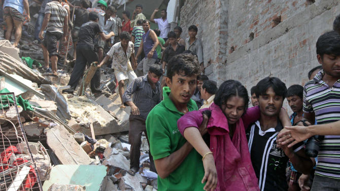 Rescuers assist an injured woman after an eight-story building housing several garment factories collapsed in Savar, near Dhaka, Bangladesh, Wednesday, April 24, 2013. Dozens were killed and many more are feared trapped in the rubble. (AP Photo/ A.M. Ahad)