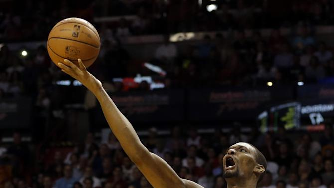 Miami Heat's Chris Bosh (1) shoots in front of Golden State Warriors' David Lee (10) during the first half of an NBA basketball game, Thursday, Jan. 2, 2014, in Miami