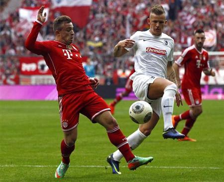 Bayern Munich's Shaqiri is tackled by Freiburg's Schmid during their German Bundesliga first division soccer match in Munich
