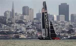 Oracle Team USA sails against the city skyline against Emirates Team New Zealand during Race 3 of the 34th America's Cup yacht sailing race in San Francisco