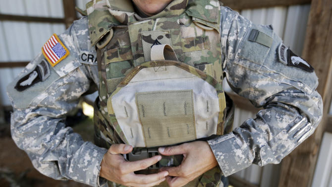 Sgt. Bobbie Crawford removes her new body armor after training on a firing range on Tuesday, Sept. 18, 2012, in Fort Campbell, Ky. Female soldiers from 1st Brigade Combat Team, 101st Airborne Division are field testing the first Army body armor designed to fit women's physiques in preparation for their deployment to Afghanistan this fall. (AP Photo/Mark Humphrey).