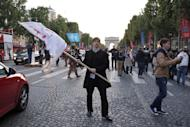 """A supporter of the French anti-gay marriage movement """"La Manif Pour Tous"""" attempts to hold an unauthorised demonstration on the Avenue des Champs-Elysees in central Paris on May 25, 2013"""
