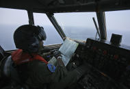 "An Indonesian Navy pilot checks his map during a search operation for the missing Malaysian Airlines Boeing 777 over the waters bordering Indonesia, Malaysia and Thailand near the Malacca straits on Monday, March 10, 2014. Dozens of ships and aircraft have failed to find any piece of the missing Boeing 777 jet that vanished more than two days ago above waters south of Vietnam as investigators pursued ""every angle"" to explain its disappearance, including hijacking, Malaysia's civil aviation chief said Monday. (AP Photo/Binsar Bakkara)"