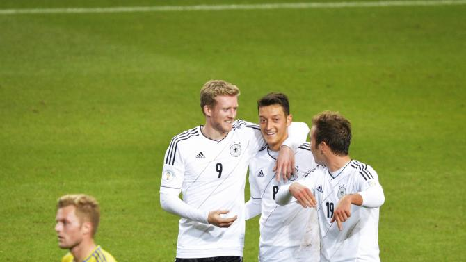 Germany's Andre Schuerrle, left, celebrates with teammates Mesut Ozil, center, and Mario Goetze after scoring his third goal while Sweden's Sebastian Larsson, bottom left,  looks on during the 2014 World Cup group C qualifying soccer match between Sweden and Germany at Friends Arena in Stockholm, Sweden, Tuesday, Oct. 15, 2013