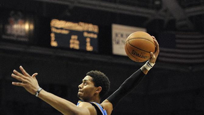 Oklahoma City Thunder's Jeremy Lamb dunks the ball over in front of Milwaukee Bucks' Gary Neal (12) during the first half of an NBA basketball game Saturday, Nov. 16, 2013, in Milwaukee