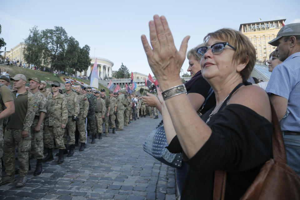 People applause to members of the Right Sector group march down the street during a rally in the center Kiev, Ukraine, Tuesday, July 21, 2015. The ...