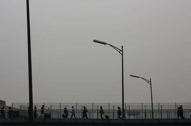 People walk on a bridge connected to a subway station amid heavy haze in Beijing