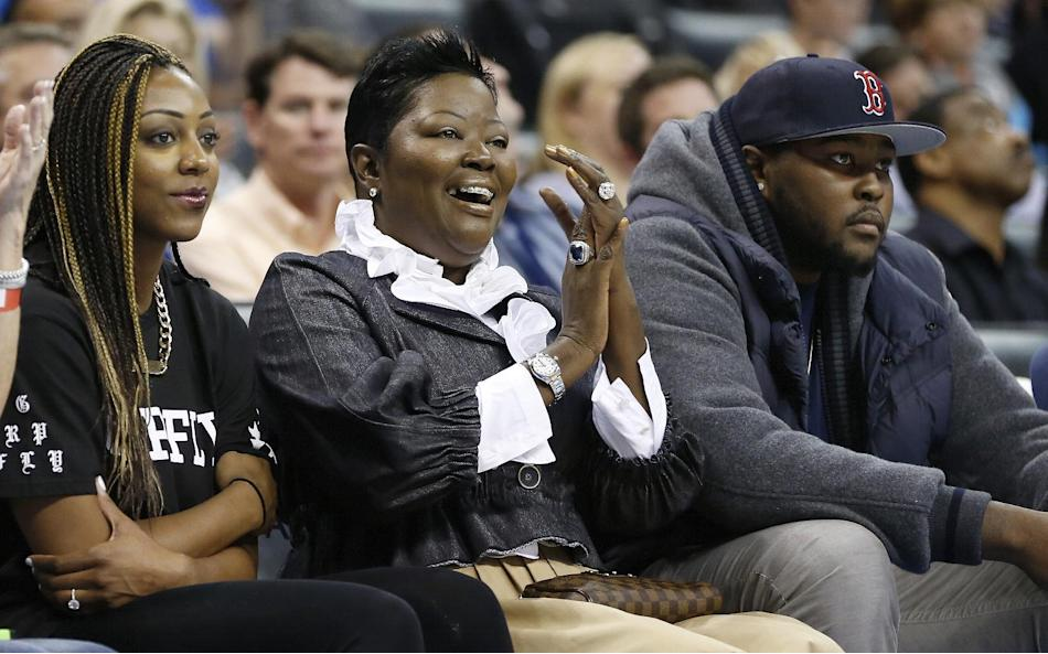 Wanda Pratt, center, Kevin Durant's mother, applauds as she sits between Tony Durant, right, Kevin's brother, and Kevin's fiancee, Monica Wright, left, during the second quarter of a preseason NBA bas