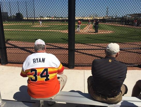 A fan wearing a Nolan Ryan jersey sits next to Nolan Ryan himself at Astros camp. (@brianmctaggart)